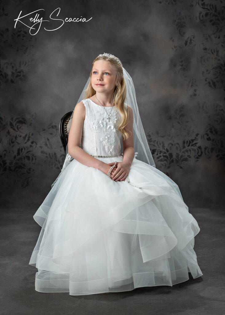 Studio communion portrait of little girl in formal white dress, veil and crown, smiling, sitting in chair, looking up off to the side