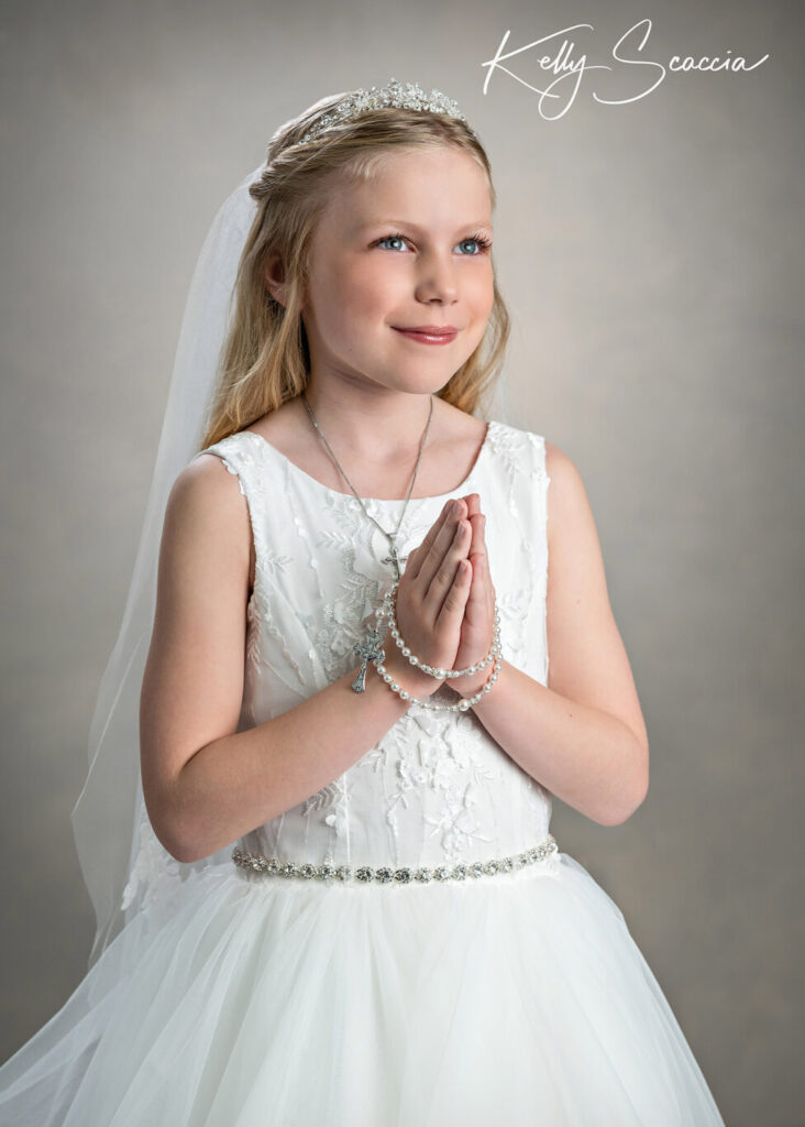 Studio communion portrait of little girl in formal white dress, veil and crown, smiling, hands in prayer wrapped with rosary, looking up at light