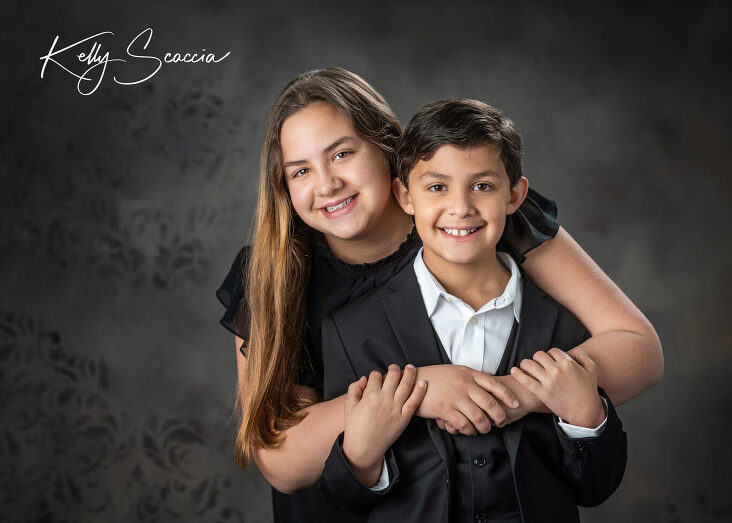 Studio portrait of brother and sister hugging eachother, smiling, looking at you