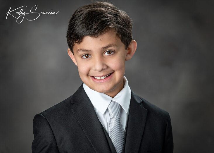 Studio communion boy portrait wearing a black suit, gray tie, looking at you, smiling
