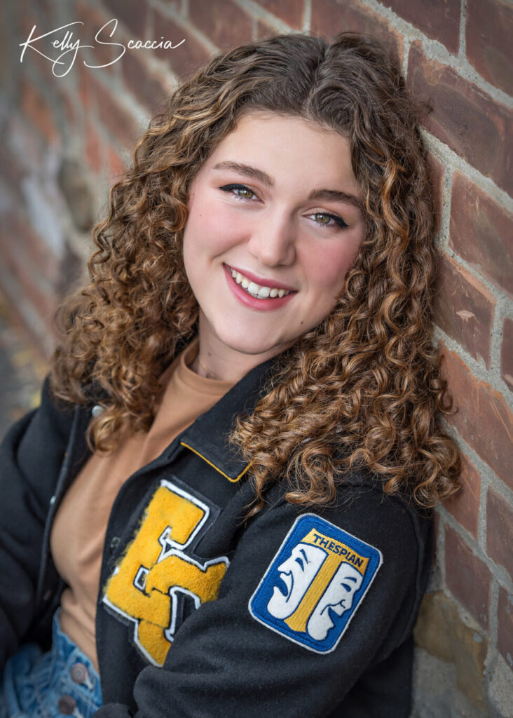 Senior girl outdoor portrait with long, brown, curly hair, smiling, looking at you, wearing varsity jacket and jeans