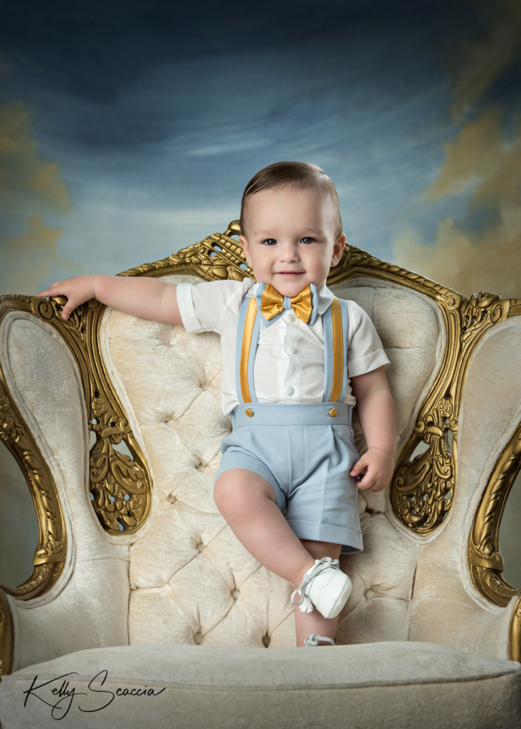 Smiling baby boy standing on ornate white chair with gold trim wearing light blue shorts and white shirt with suspenders and bow tie