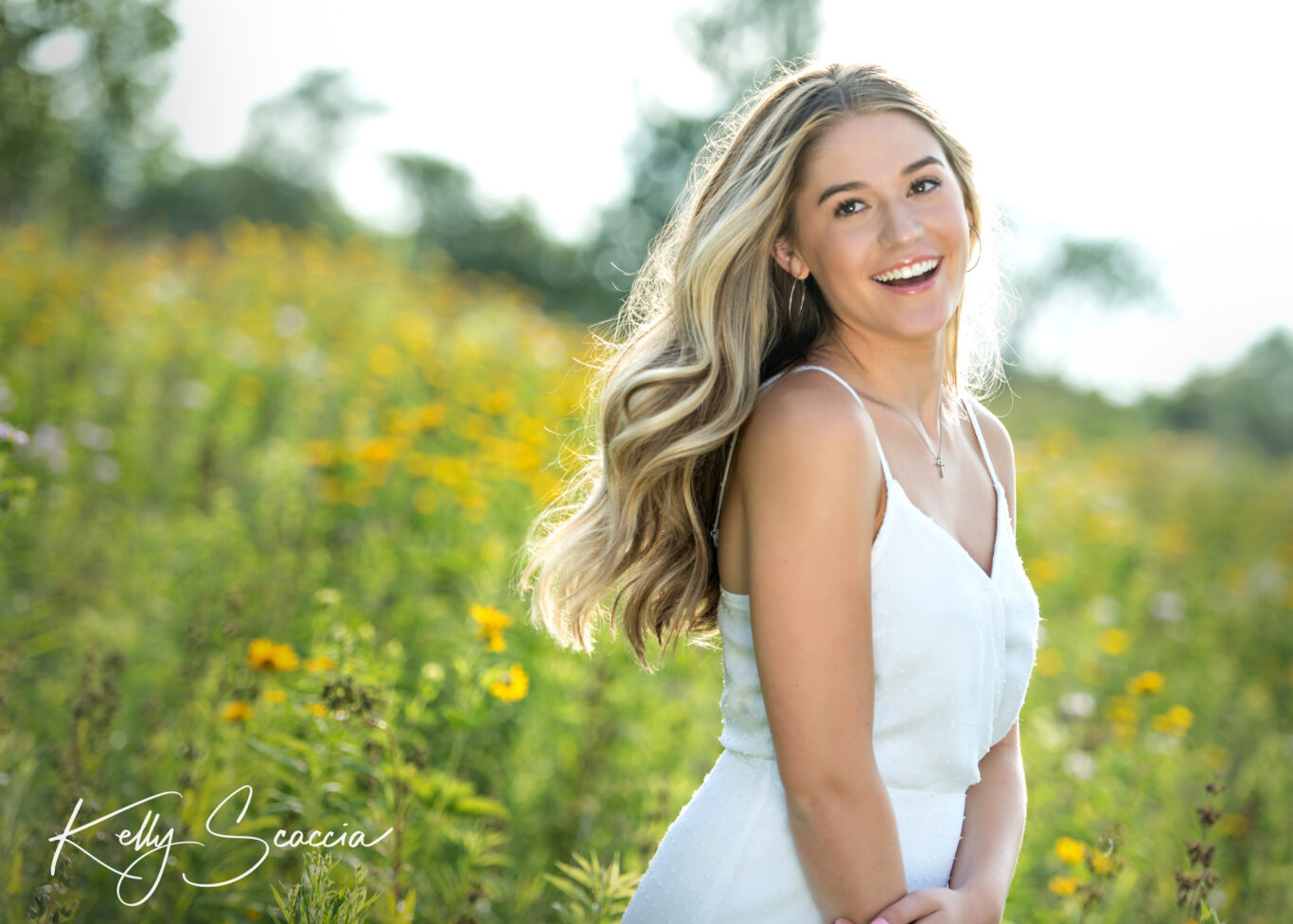 Long blond hair girl smiling in a field looking off to the side wearing a white spaghetti strap dress
