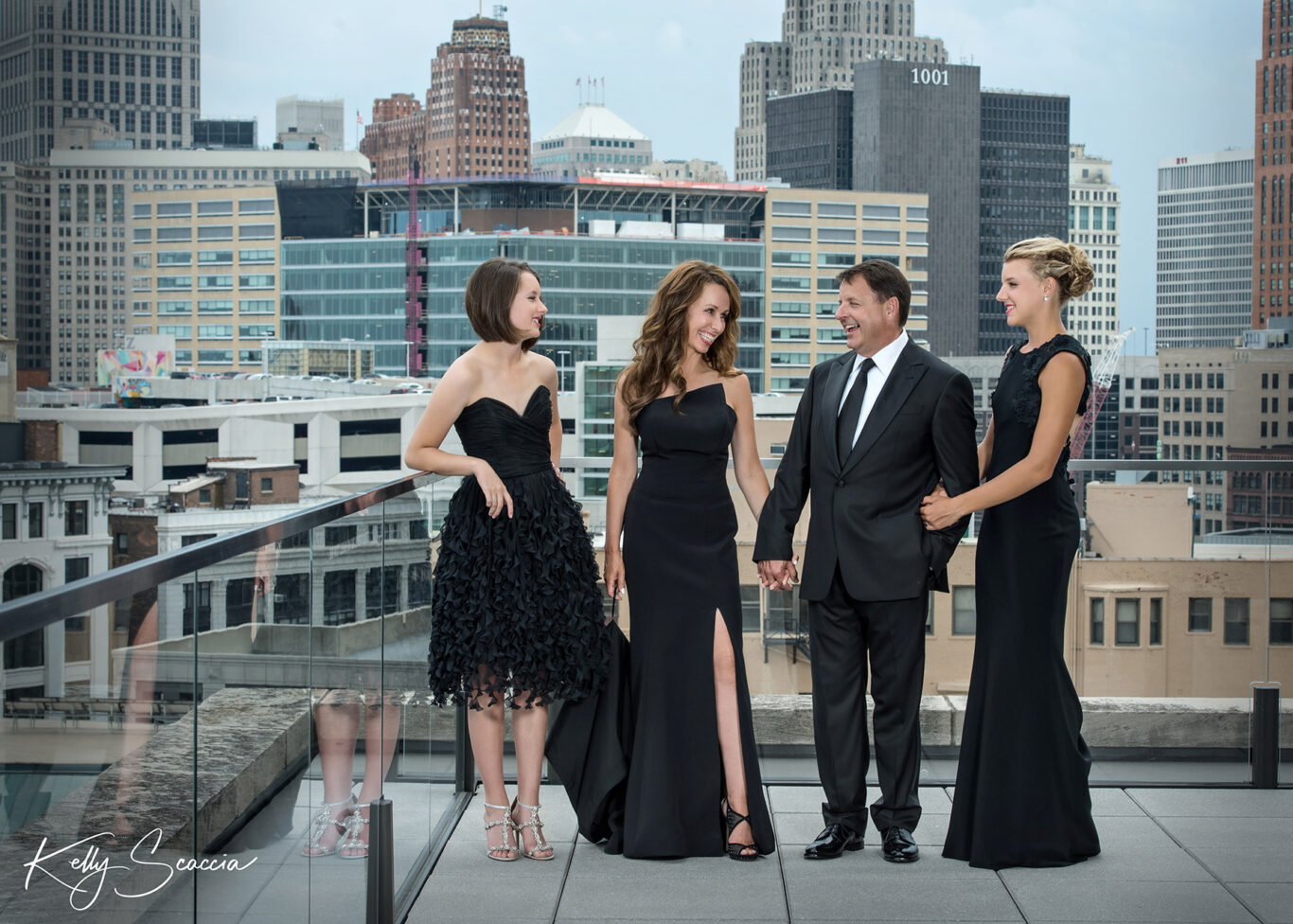 Family of four dressed formal on top of a skyscraper in a city landscape looking at one another smiling