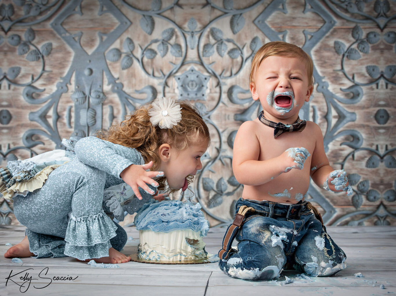 Little boy crying with cake on his face while his sister takes over the cake and begins to lick it
