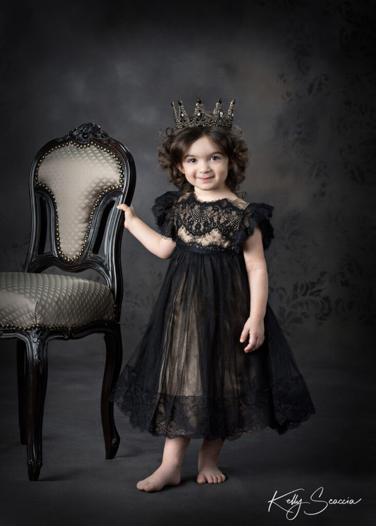 Little girl in black formal gown with black crown smiling and holding on to side of beige chair